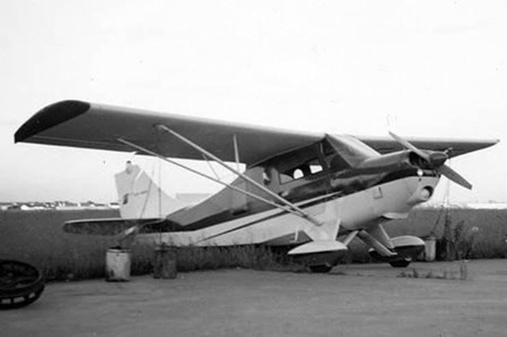 7KC-Olympia parked on a weedy ramp. BW photo.